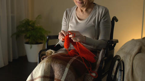 Disabled woman knitting in room and smiling, financially secure old age, hobby Live Action