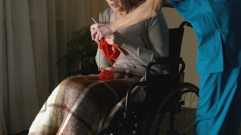 Nurse taking away needles from woman with Parkinsons disease trying to knit Footage