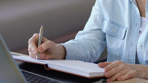 Business woman writing down to notebook plan for near future, making schedule Live Action