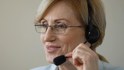 Friendly smiling old woman in headset speaking with client, call center support Footage
