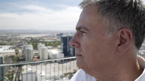 Man Looking At The City Below Him On The Rooftop Of A Hotel 4k stock footage