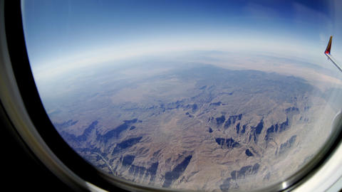 fisheye view of a mountain range out of a passenger jet window 4k Footage