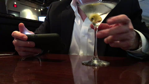 man in a restaurant texting on his smart phone and drinking a martini Footage