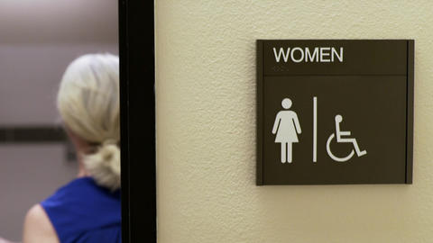 woman walking into a womans restroom in an office Footage