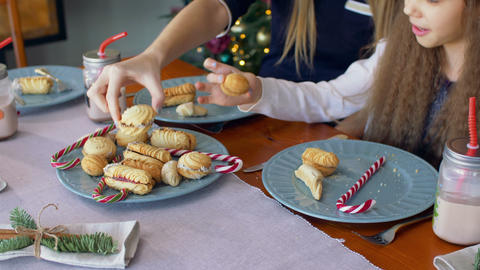Hands taking christmas cookies and candy from plate Footage