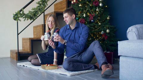 Happy couple enjoying hot drink under christmas tree Footage