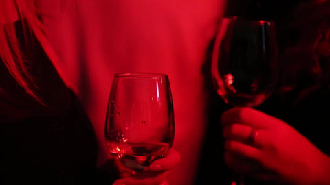 Close-up of girls hands holding a glass of alcohol. Red background Live Action