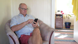 Happy Senior Man Using Phone On The Couch At Home Footage