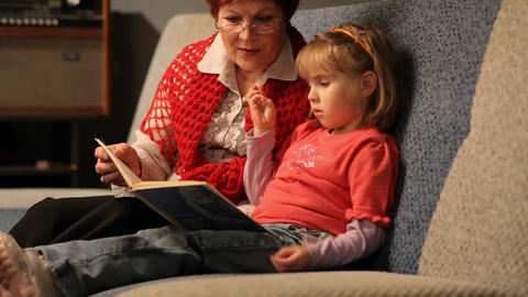 Grandmother reading a tale to her baby granddaughter Live Action