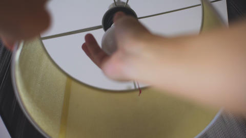 Man putting in lamp energy saving light bulb, rational electricity consumption Live Action