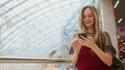 Girl use mobile phone, blur image of inside the mall as background Live Action