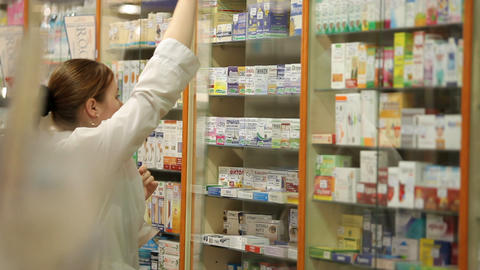 Woman pharmacist holding prescription checking medicine in pharmacy Footage