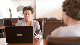 Happy Mature Businesswoman Using Technology While Talking With Senior Woman Footage