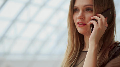 Young attractive girl goes shopping in mall, talking on phone, shopping concept Footage