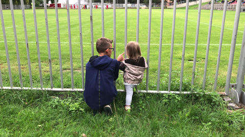 Boy points out and explains rules to girl at football match from behind fence Archivo