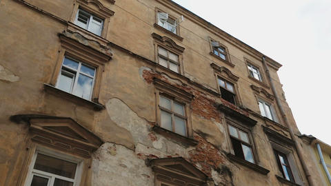Aged building facade with broken windows in old historical town, loneliness Footage