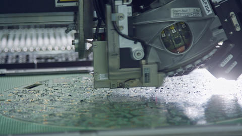 Close up of SMT Machine placing components on a circuit board Live Action