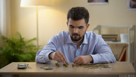 Worried bachelor counting money on table, price inflation, low-paid job, savings Footage