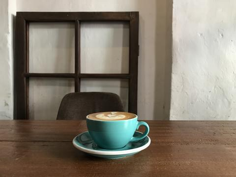 hot cappuccino on table with brown chair and antique wooden window frame as フォト