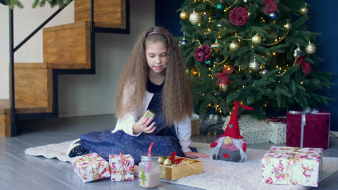 Little girl decorating christmas tree with toys Footage