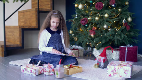 Positive girl reading a book under christmas tree Footage