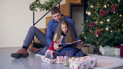 Joyful family reading fairy tale at christmas time Footage