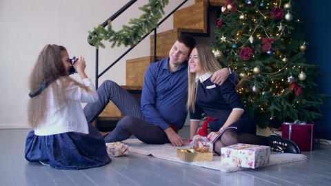 Girl taking pictures of her happy parents at Xmas Footage