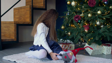 Little girl looking for gifts under Christmas tree Footage