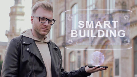 Smart young man with glasses shows a conceptual hologram Smart building Live Action