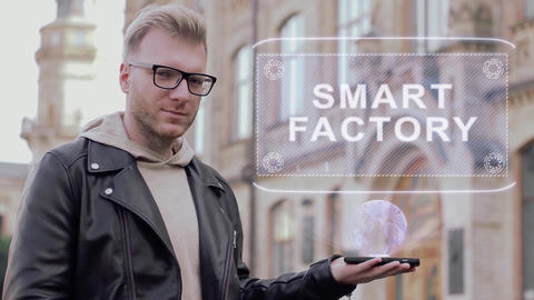 Smart young man with glasses shows a conceptual hologram Smart Factory Live Action