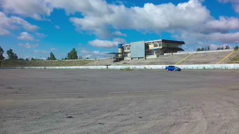 Car driving on race circle on abandoned autodrome with blue sky background Footage