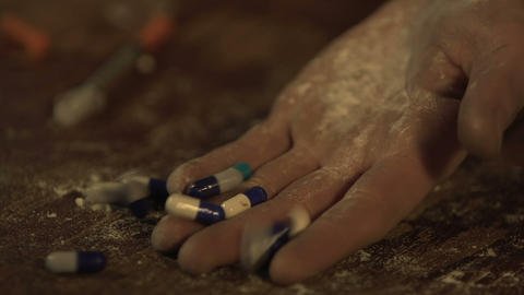 Man committing suicide, hand full of pills falling on floor closeup overdose Live Action