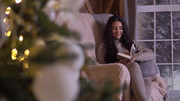 A girl sits in a chair near the Christmas tree and reads a book Footage
