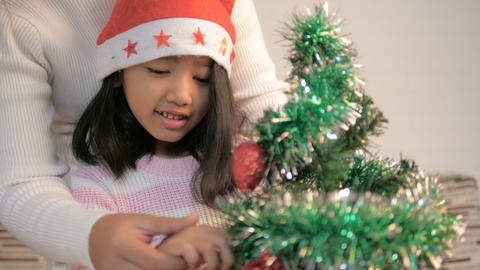 Asian little girl decorating the Chistmas tree Footage