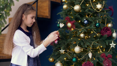 Cute girl decorating xmas tree with colorful bauble Footage