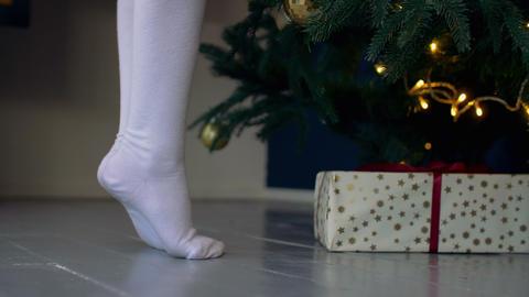 Kid standing on tiptoes near Christmas tree Footage