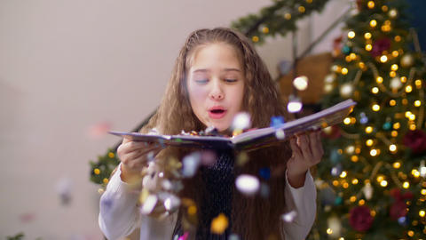 Adorable girl blowing glitter confetti from book Footage