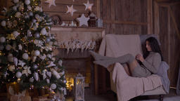 A girl drinks tea sitting in a chair near the Christmas tree on Christmas day Archivo