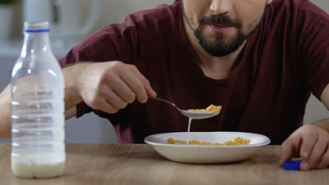 Male pouring milk and eating cereal breakfast with pleasure, healthy nutrition Footage