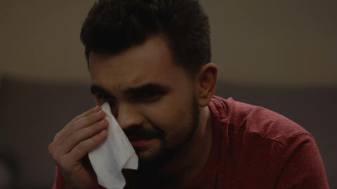 Vulnerable and gentle man wiping tears in his eyes, watching soap opera on tv Live Action