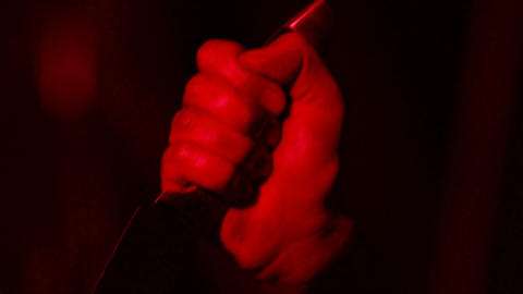 Male hand killing with knife, cold-blooded massacre, scary thriller, closeup Live Action