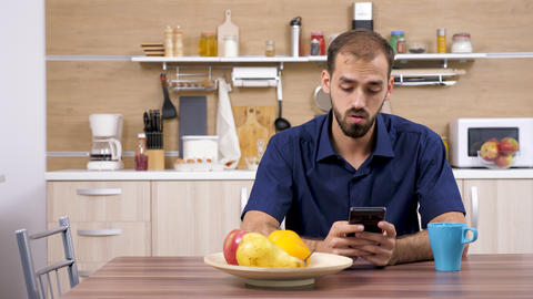Man at the table in the kitchen using a smartphone Footage