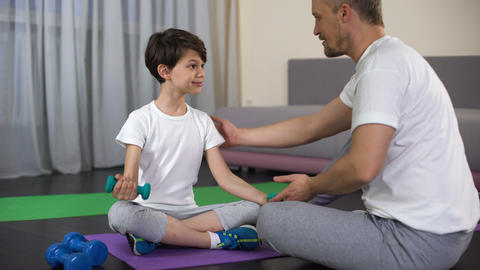 Sportive dad teaching his son to make dumbbells exercise at home, muscles power Live Action