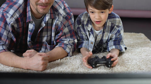 Man supporting his little son playing video game at home, family relationship Live Action