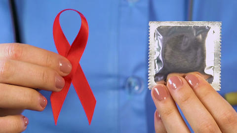 Nurse giving people condoms and red ribbons social campaign against HIV and AIDS Footage