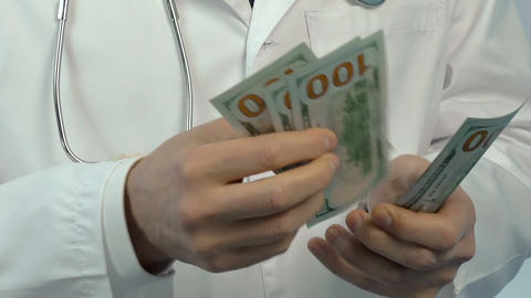 Corrupt doctor counting money, bribery in healthcare and medicine closeup Live Action