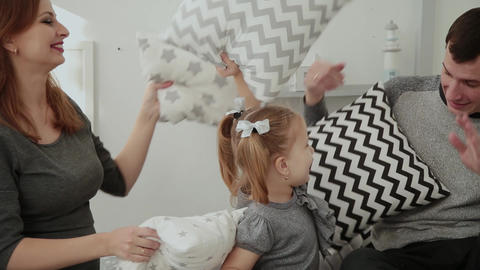 Merry family throws pillows into each other in the New Year s room GIF