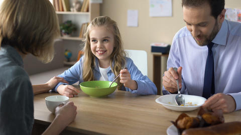 Friendly family eating breakfast and talking, morning ritual, togetherness Footage