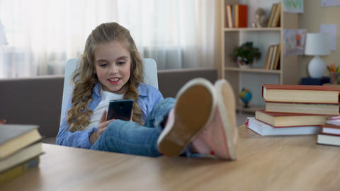 Smiling child sitting at table and playing game on smartphone, gadget addiction Live Action