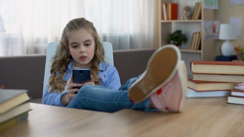 Little girl actively playing games on smartphone at home, gadget addiction Live Action